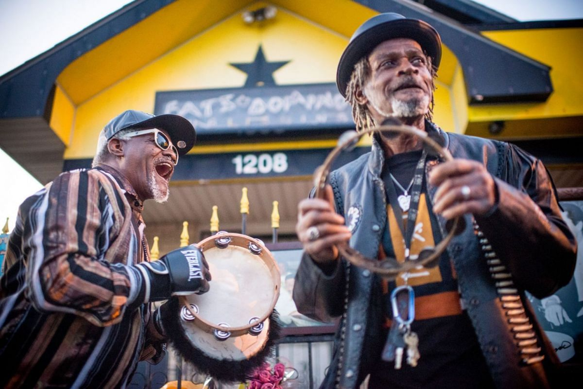 Ricky Gettridge (L) and Luqman Asadullah, lifelong friends of Fats Domino, sing and play tambourine to Fats's songs at a memorial outside of his old home in the Lower 9th Ward in New Orleans, Louisiana, on October 25, 2017. Fats Domino died on Octobe