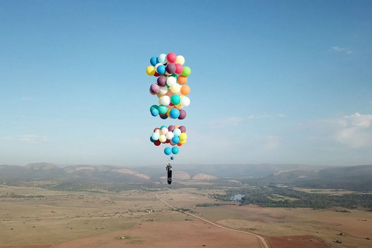 A handout photo released today, October 26, 2017, shows Tom Morgan, from Bristol-based company The Adventurists, flying in a chair with large party balloons tied to it near Johannesburg, South Africa, October 20, 2017. PHOTO: REUTERS/ THE ADVENTURIST