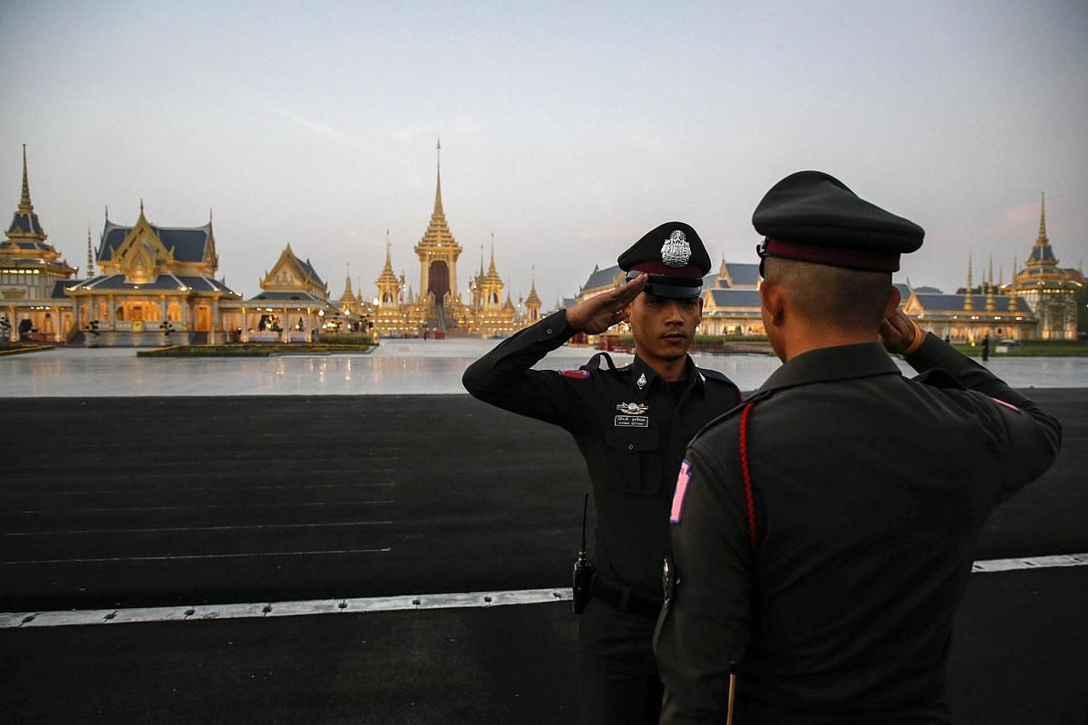 Thai police officers salute each other during security preparations for the royal cremation ceremony outside the Royal Crematorium at Sanam Luang in Bangkok.