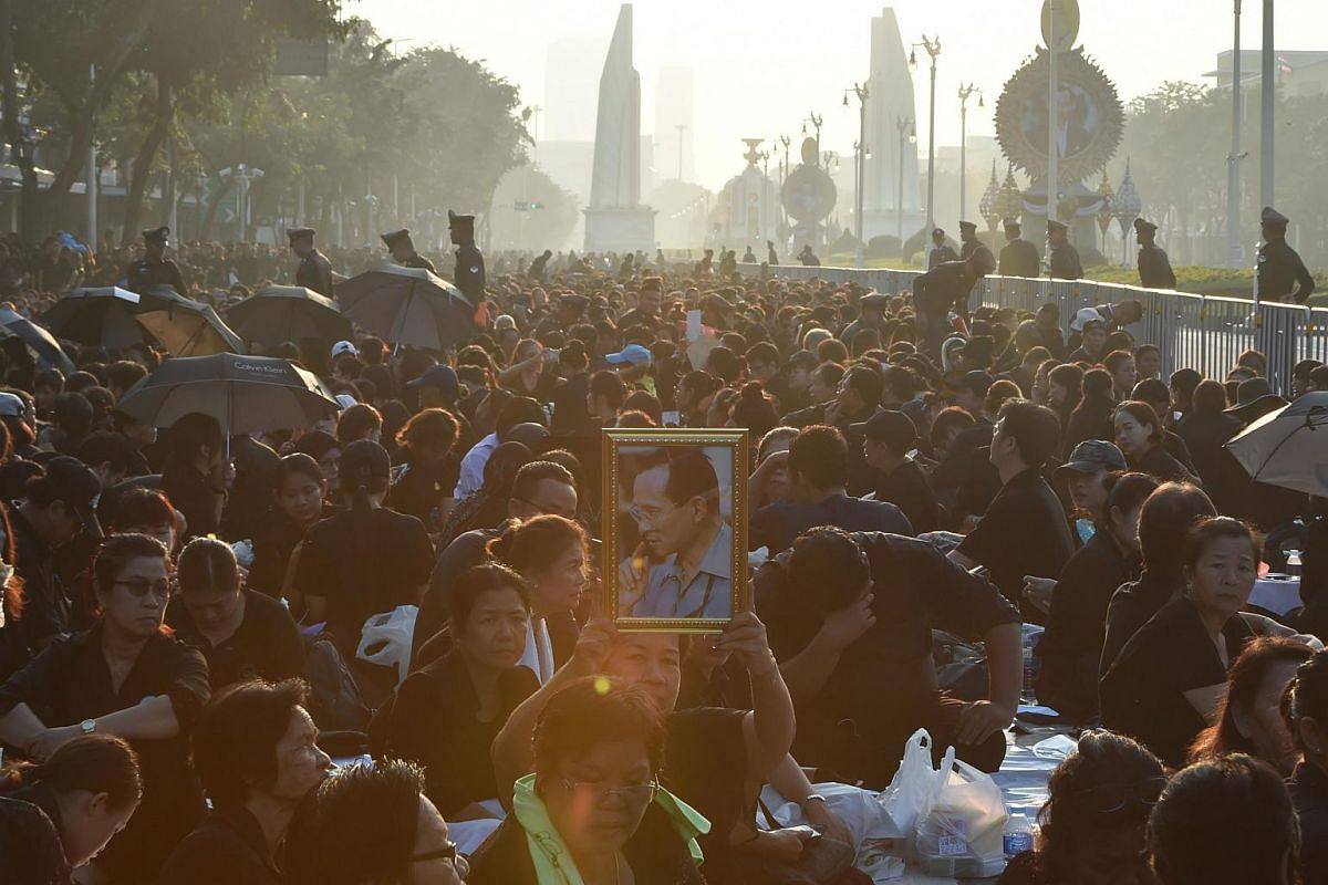 A mourner holds a potrait of the late Thai King Bhumibol Adulyadej as she and others wait for his funeral procession to take place outside the Grand Palace in Bangkok.