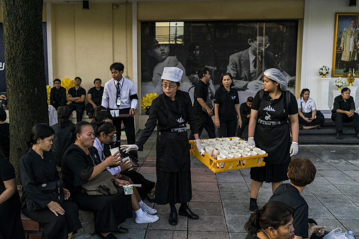 Volunteers handing out drinks to mourners who spent the night waiting to attend the cremation of King Bhumibol Adulyadej in Bangkok.