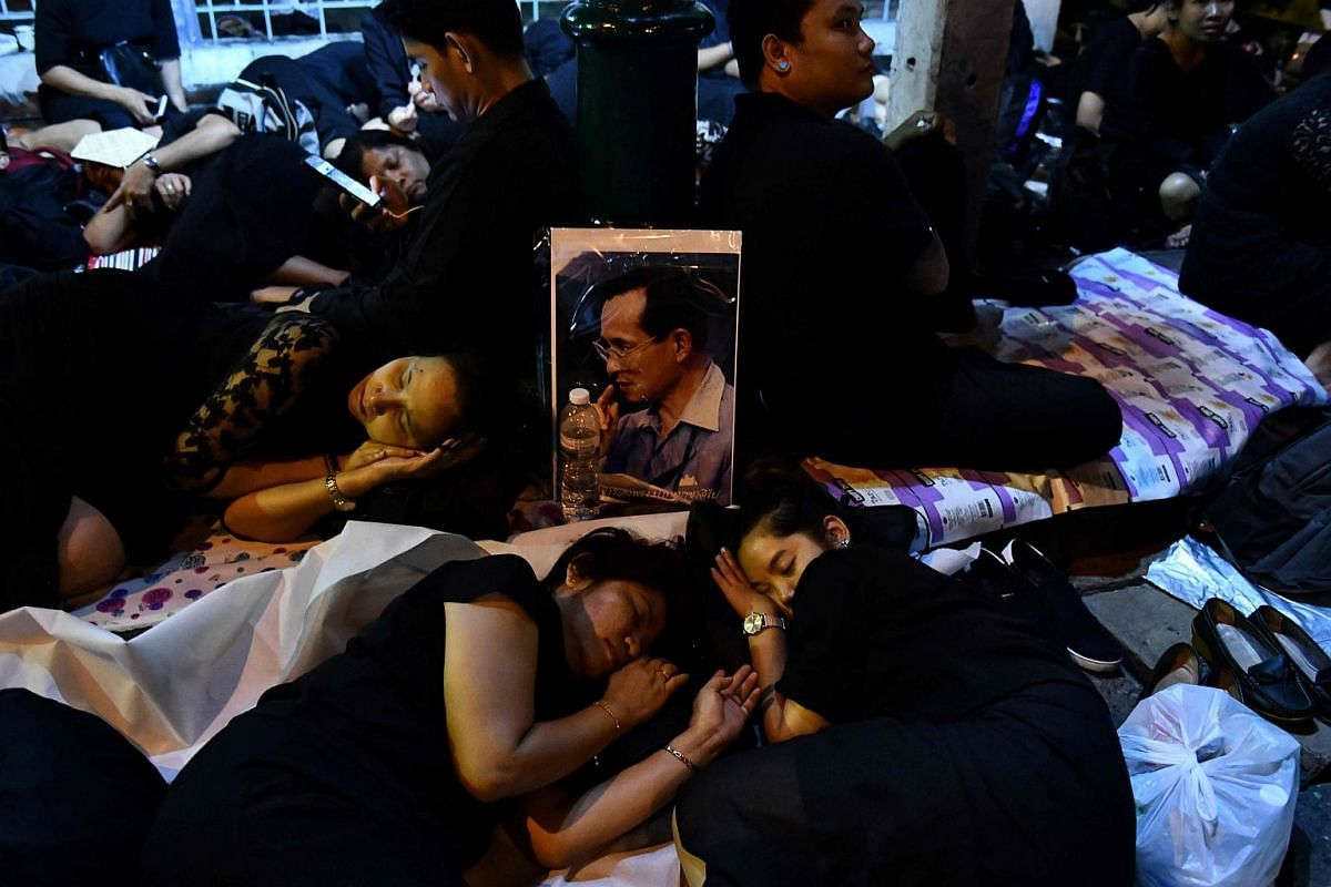 Mourners sleep in front of an image of the late Thai King Bhumibol Adulyadej as they wait for his funeral procession to take place in Bangkok.