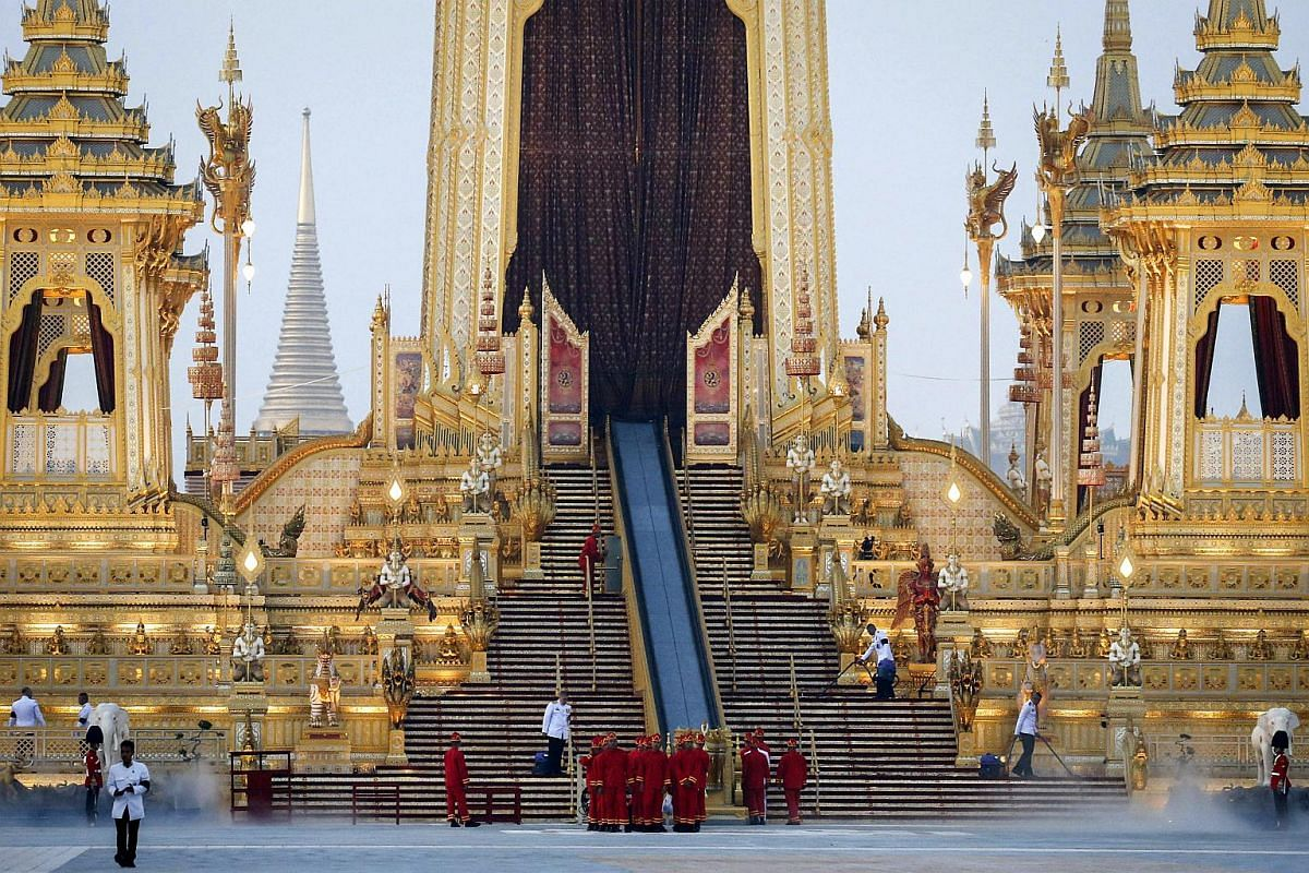 Officers clean up the area during the preparations for the royal cremation ceremony outside the Royal Crematorium at Sanam Luang in Bangkok.