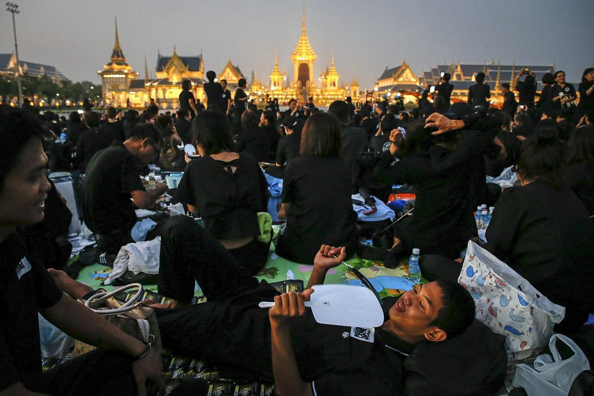 Thai mourners wait for the royal cremation ceremony outside the Royal Crematorium at Sanam Luang in Bangkok.