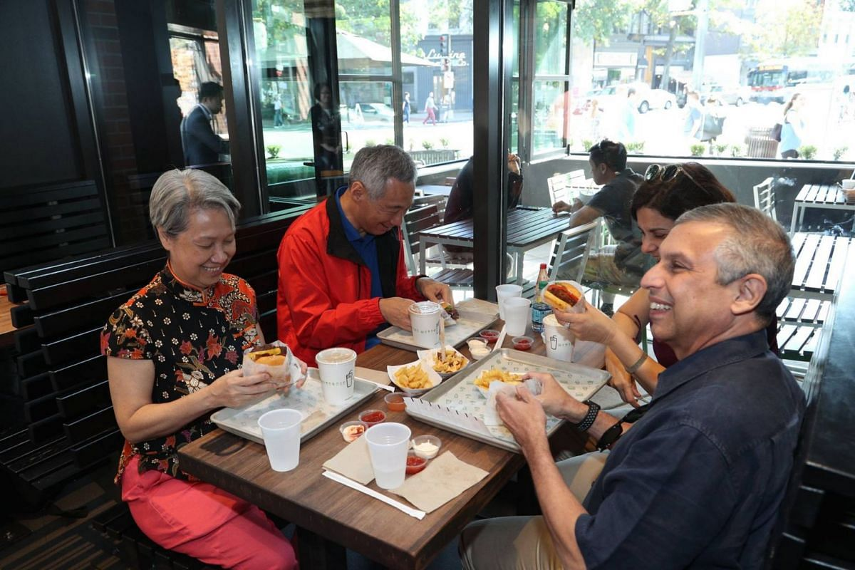 Ambassador Mirpuri (right), PM Lee and Mrs Lee try out some burgers at Shake Shack.
