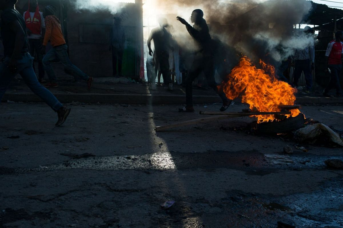 Supporters of the opposition coalition the National Super Alliance (NASA) and its presidential candidate Raila Odinga, throw stones and taunt police during a protest in Mathare slum, one of the opposition strongholds in Nairobi, Kenya, 26 October 201