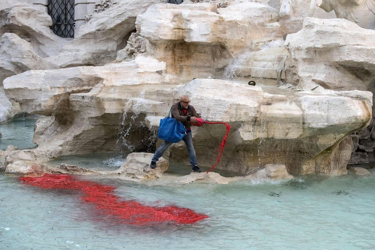 Activist Graziano Cecchini pouring red paint in the water of Trevi fountain in Rome, Italy, as a protest against Rome's corruption, October 26, 2017. PHOTO: EPA-EFE