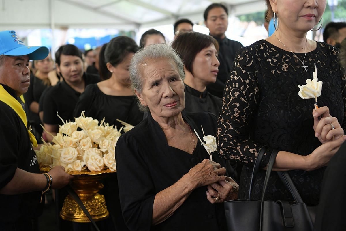 Mourners placing sandalwood flowers in front of the late Thai King Bhumibol Adulyadej's portrait at the Royal Thai Embassy in Orchard Road on October 26, 2017. The proceedings in Bangkok were also broadcast live. PHOTO: THE STRAITS TIMES/ NG SOR LUAN