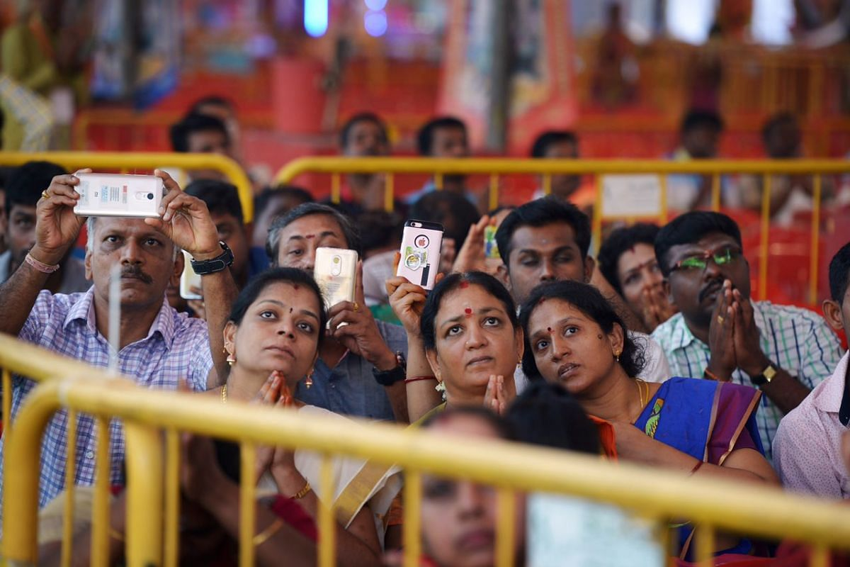 Devotees trying to get a glimpse of the action at the consecration ceremony.