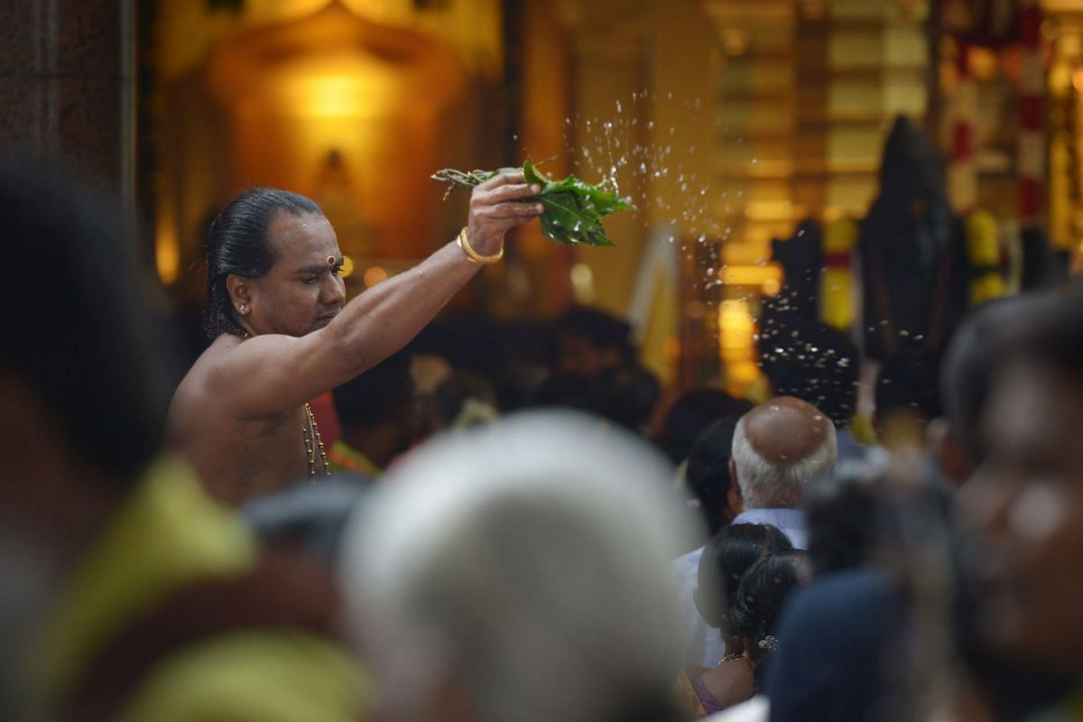 A priest sprinkles water on devotees who are lining up to pray before the shrine at the consecration ceremony.