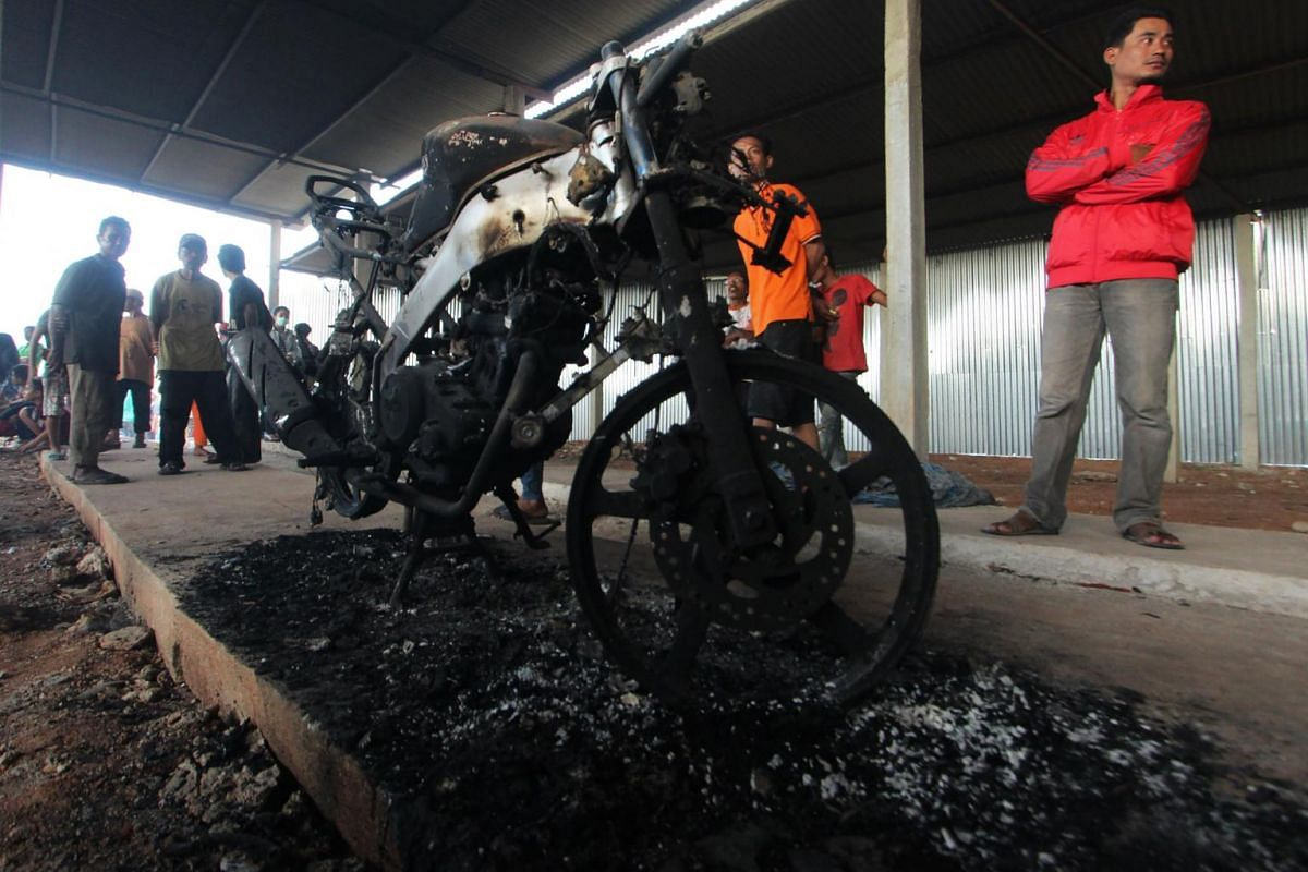 People stand near a burnt motorcycle after the explosion.