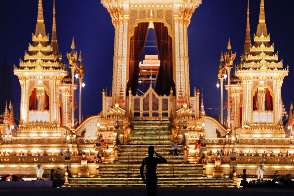 A soldier salutes in front of the Royal Crematorium.