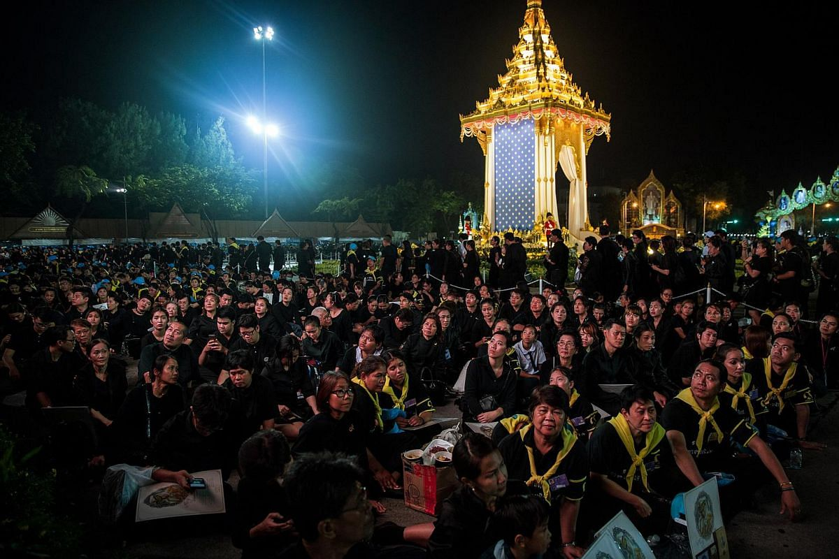 Mourners watching the royal cremation ceremony that was being shown on a large screen.