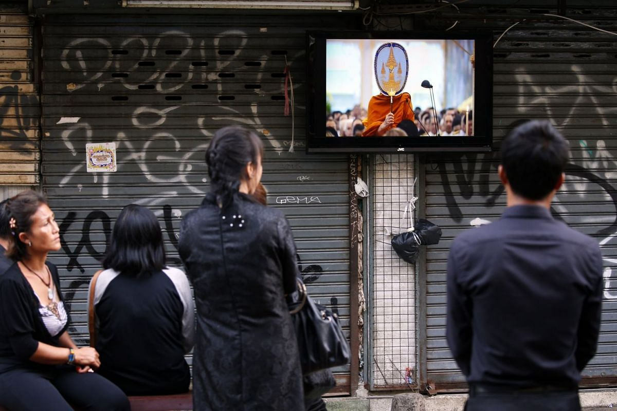 Thai mourners watch the royal cremation ceremony on a television at a shop on the popular backpacker street Khao San road in Bangkok.