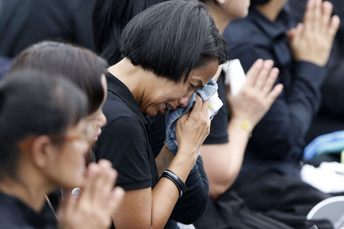 Grieving Thais break into tears while the royal urn of the late Thai King Bhumibol Adulyadej is elevated into a cremation chamber.