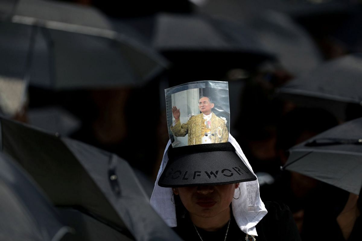 A mourner wearing a hat decorated with a picture of Thailand's late King Bhumibol Adulyadej.