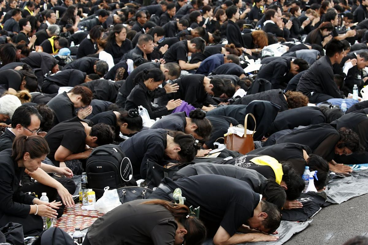 Mourners prostrating themselves in an act of reverence to King Bhumibol as the royal urn arrived at the crematorium. Many people slept in the open for days and camped out on sidewalks to secure a viewing spot for the ceremony.