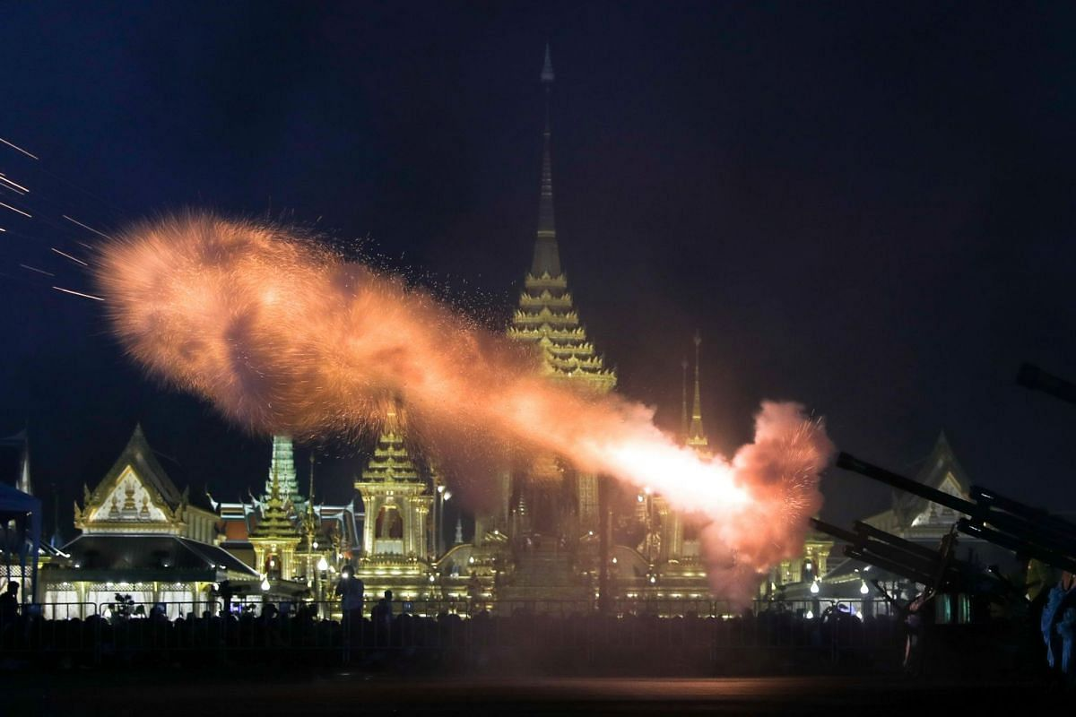 Thai royal guards firing a salute during the symbolic royal cremation at the royal crematorium site near the Grand Palace last night.