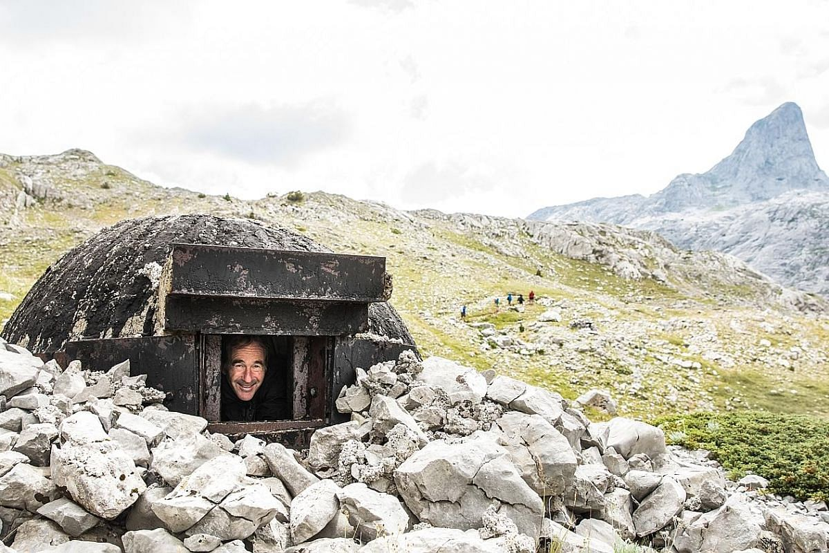 Clamber into pillboxes built decades ago by Albania's communist dictator Enver Hoxha to defend the borders of his country. The writer (right), with his guide and translator, chats with an elderly woman who tells him of the Kanun, a 400-year-old code