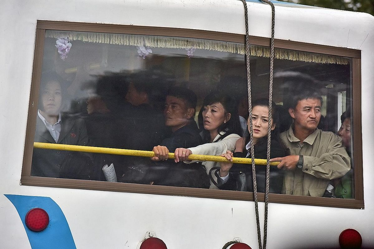Housewives in olive-green uniforms waving flags in Pyongyang to encourage workers on their way to factories in the morning. From top: A nurse comforting a child at a Pyongyang orphanage. Some children there suffer from malnutrition. There are smartly