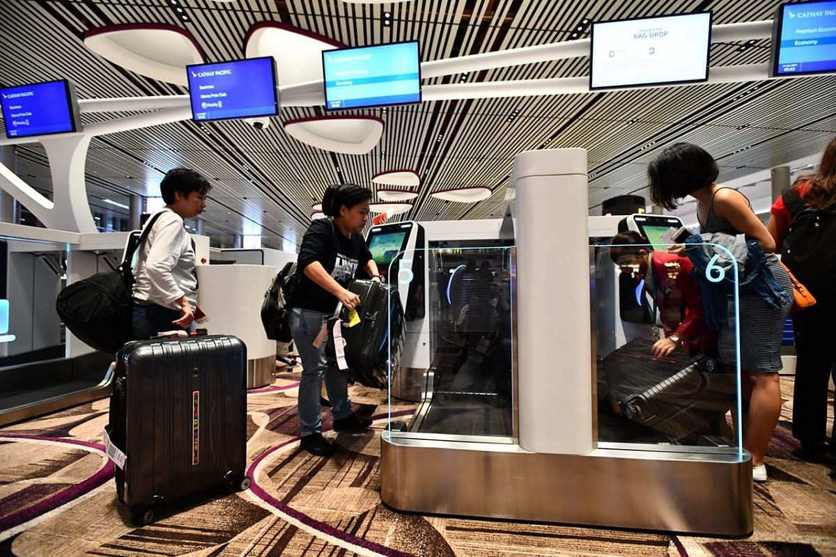 Passengers from first flight Cathay CX650 dropping their baggage at the automated bag drop.