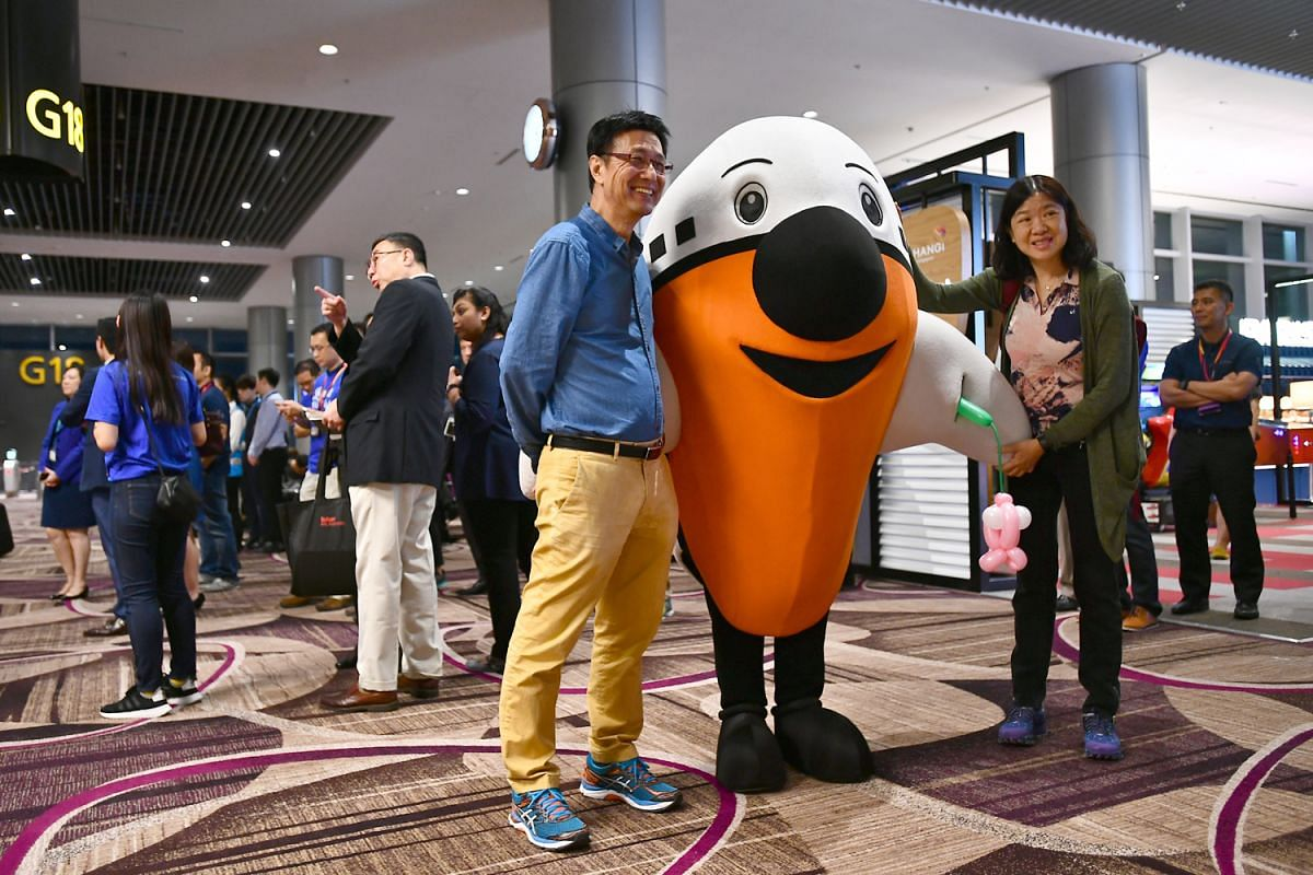 Retiree Mr Raymond Lee and Madam Eileen Kam, a manager, taking a photo with the Changi Airport mascot Max near their departure gate at Changi Airport Terminal 4 on Oct 31, 2017. Changi Airport's newest terminal - T4, started its first day of operatio