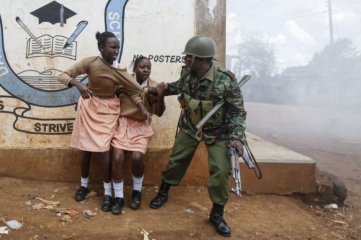 A police officer grabs school girls to get them out of the scene after they were caught up in running battles with police and protesters and was affected by tear gas in Kawangware slum, Nairobi, Kenya, 30 October 2017. PHOTO: EPA-EFE