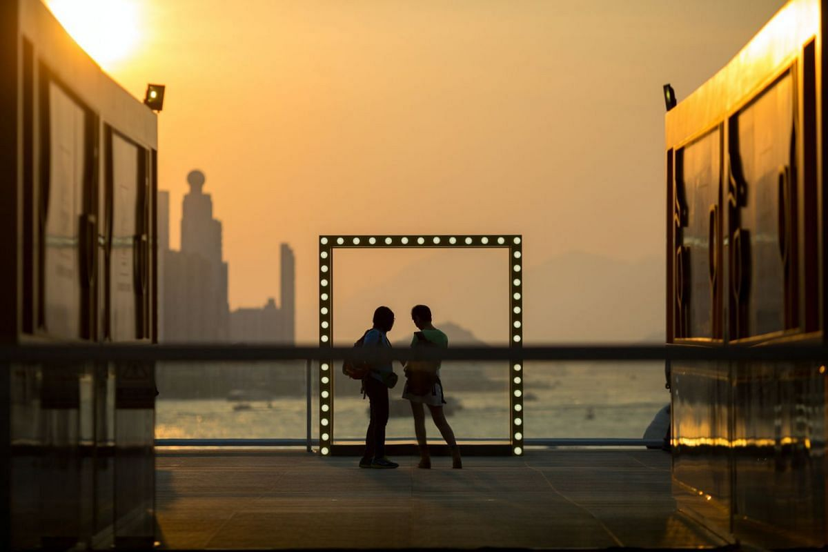 A man and a woman watch the sunset over Victoria Harbour from the Ocean Terminal Deck in Hong Kong, China, 30 October 2017. The Ocean Terminal Deck offers a 270-degree panorama of the harbour. PHOTO: EPA-EFE