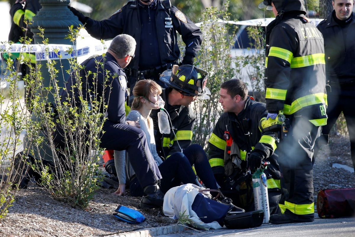 A woman is aided by first responders after sustaining an injury on a bike path in lower Manhattan in New York, NY, U.S., October 31, 2017. Eight people were killed and dozens injured after a man drove a Home Depot rental truck through a New York city