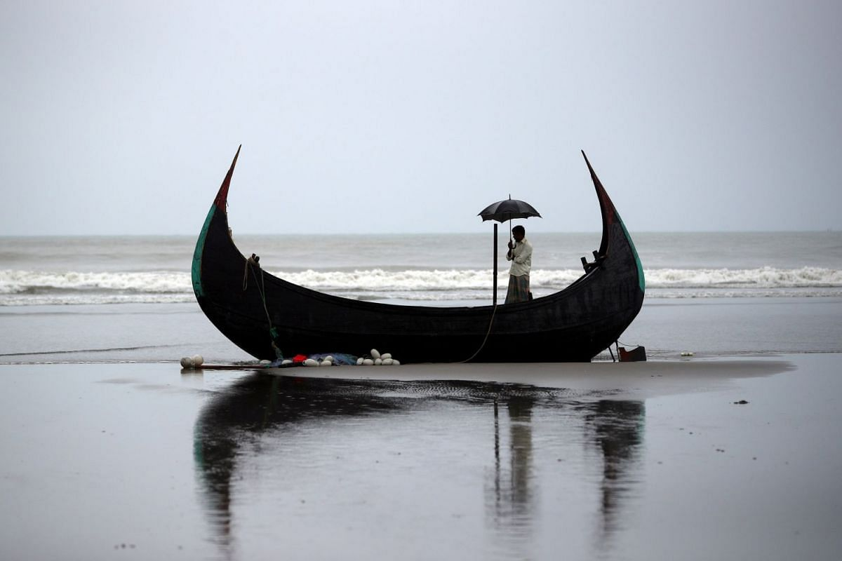 A man holds an umbrella as he stands on a boat, which capsized with a group of Rohingya refugees at Bailakhali, near Cox's Bazar, Bangladesh, October 31, 2017. PHOTO: REUTERS