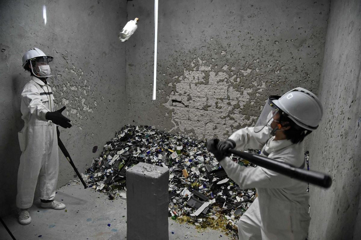 """A photograph released today Nov 1, 2017 shows Fragment Room employees smashing bottles during a demonstration in a """"rage room"""" in Singapore, October 19, 2017. Bad day at the office? In high-pressured Singapore there is now a solution -- a """"rage room"""""""