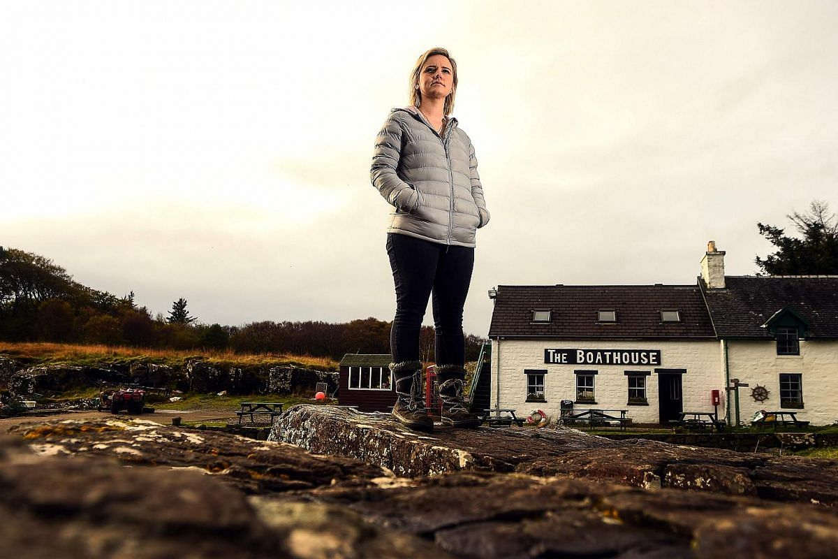 Rebecca Munro, one of the six residents of the Isle of Ulva, off Scotland's west coast poses by the shore.
