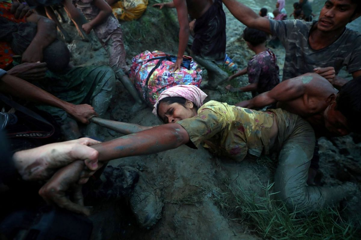 Photographers help a Rohingya refugee to come out of Nad River as they cross the Myanmar-Bangladesh border in Palong Khali, near Cox's Bazar, Bangladesh, November 1, 2017. PHOTO: REUTERS