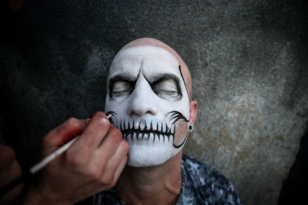 A man has his face painted as hundreds of people wearing costumes participate in the traditional 'Zombie Walk' through the streets of Sao Paulo, Brazil, November 2, 2017. The Zombie Walk is a march that has been celebrated in Brazil for a decade on t