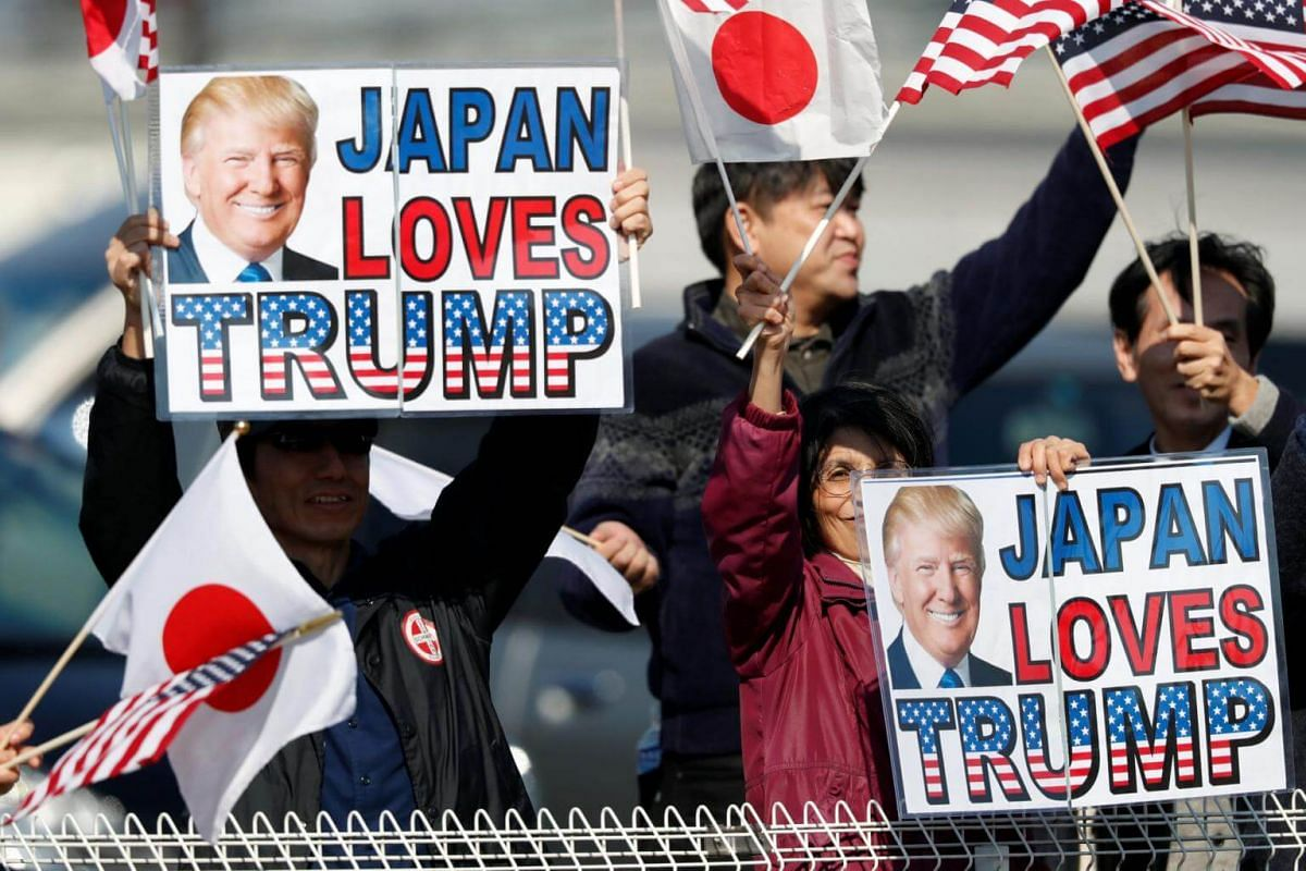 Supporters hold signs as they wait for US President Donald Trump outside Kasumigaseki Country Club in Kawagoe, Japan on Nov 5, 2017.