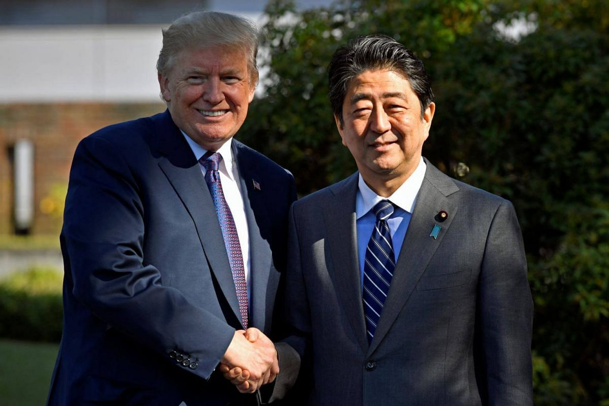 US President Donald Trump (left) shakes hands with Japan's Prime Minister Shinzo Abe as he arrives for a luncheon at the Kasumigaseki Country Club in Kawagoe, Japan on Nov 5, 2017.