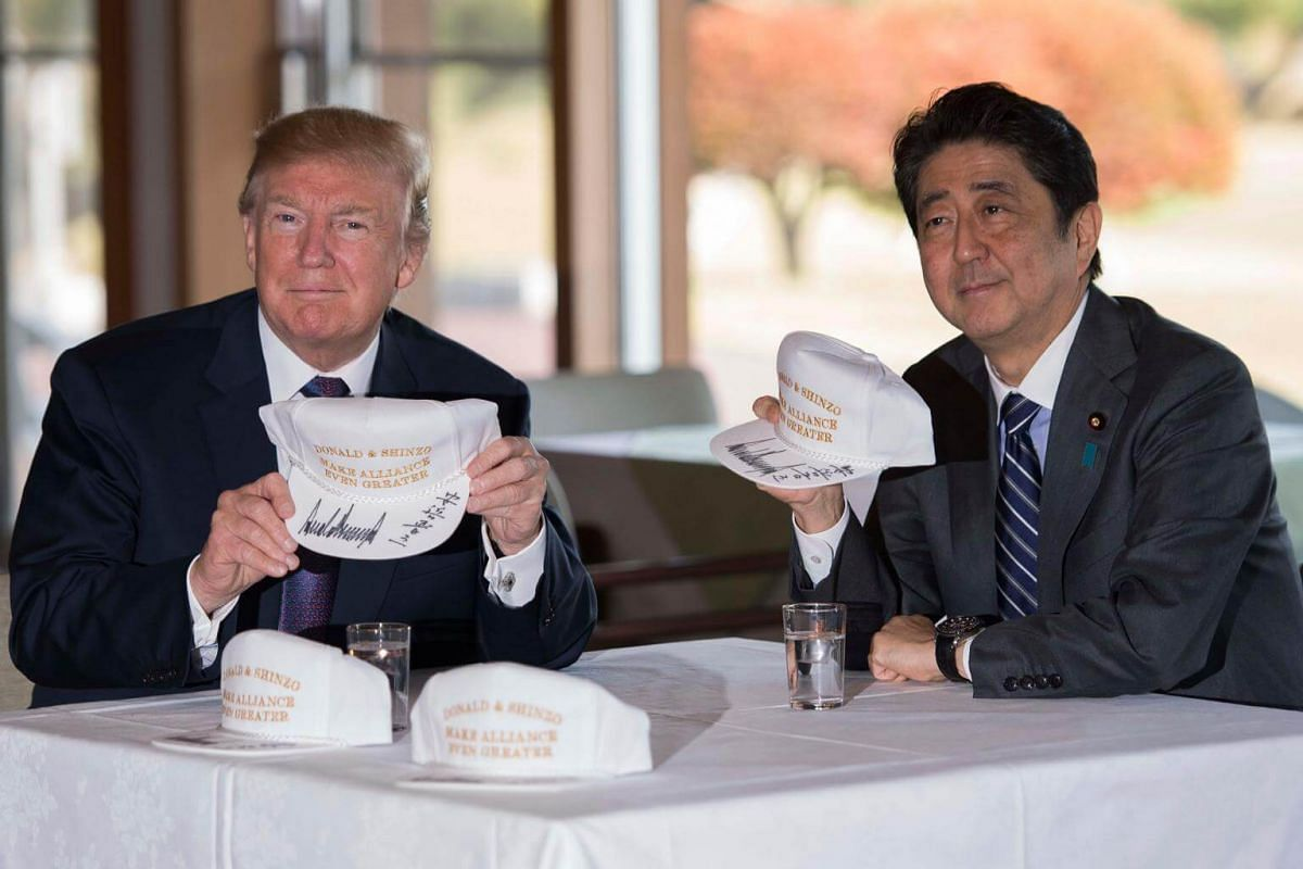 US President Donald Trump (left) holds up a hat with Japan's Prime Minister Shinzo Abe during a luncheon at the Kasumigaseki Country Club in Kawagoe, Japan on Nov 5, 2017.