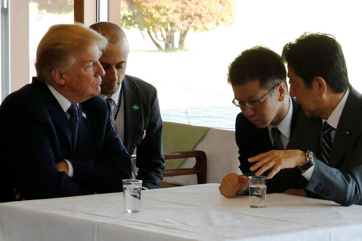 US President Donald Trump and Japan's Prime Minister Shinzo Abe speak through interpreters as they sit down to lunch before a round of golf at Kasumigaseki Country Club in Kawagoe, Japan on Nov 5, 2017.