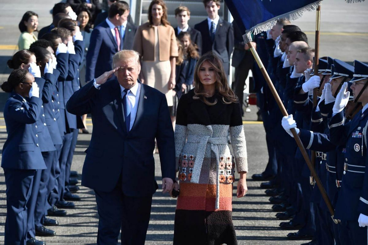 US President Donald Trump and First Lady Melania Trump walk through an honour cordon after arriving at US Air Force Yokota base in Fussa, Tokyo, on Nov 5, 2017.
