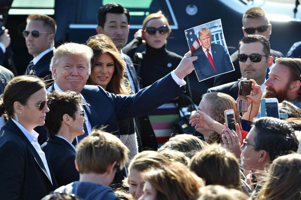 US President Donald Trump holds a photograph of himself while First Lady Melania Trump looks on, as they greet attendees after arriving at US Air Force Yokota base in Fussa, Tokyo on Nov 5, 2017.