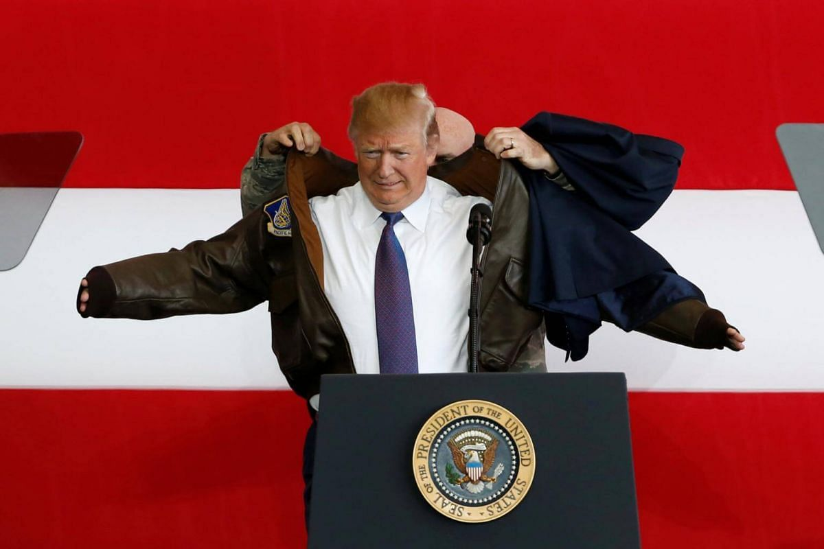 US President Donald Trump puts on a flight jacket as he arrives to address members of US military services and Japan Self-Defense Force (JSDF) at the US Air Force Yokota base in Fussa, Tokyo on Nov 5, 2017.