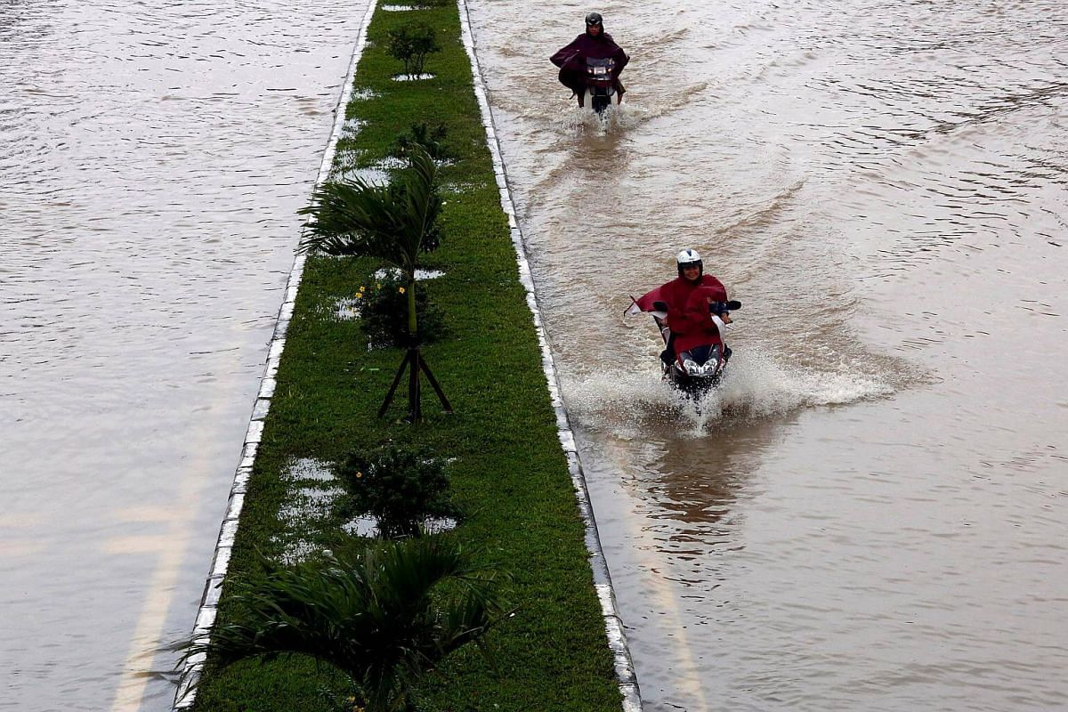 People ride motorcycles along a flooded road after Typhoon Damrey hit Vietnam in Hue city, Vietnam.