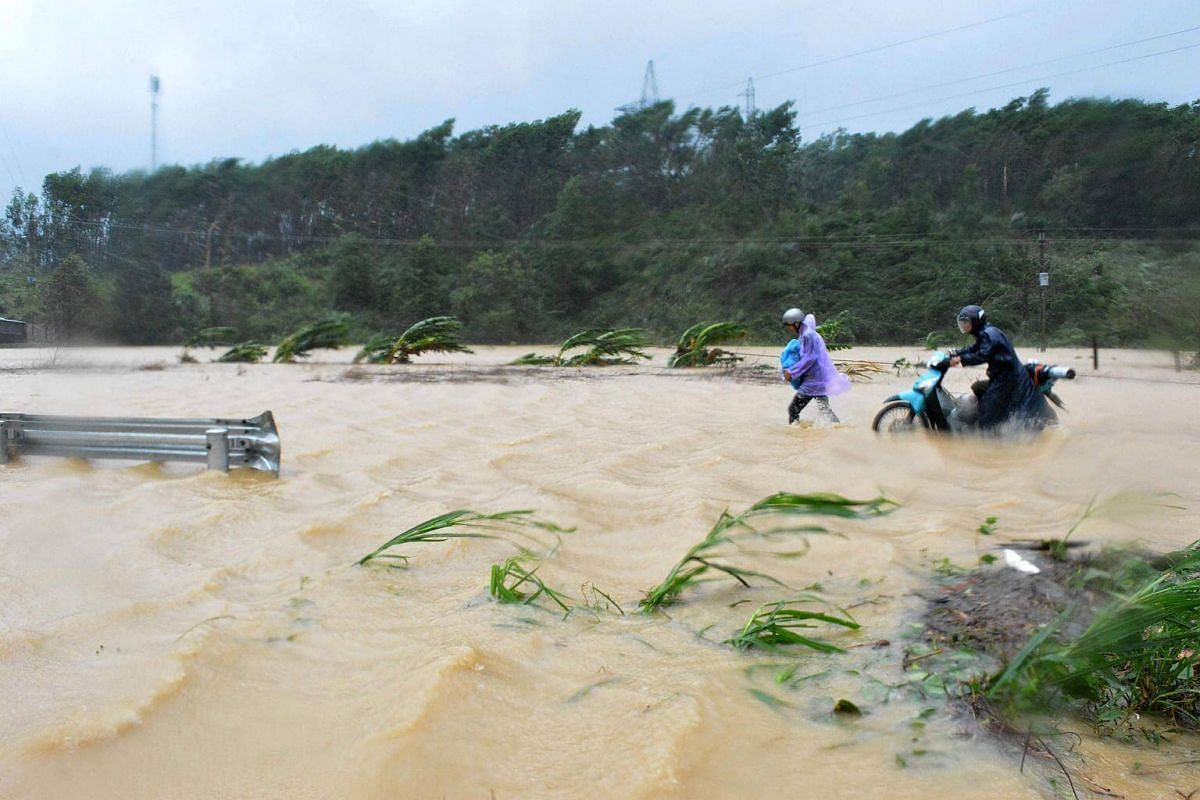 People walking through floodwaters on a highway in the central province of Dak Lak, Vietnam.