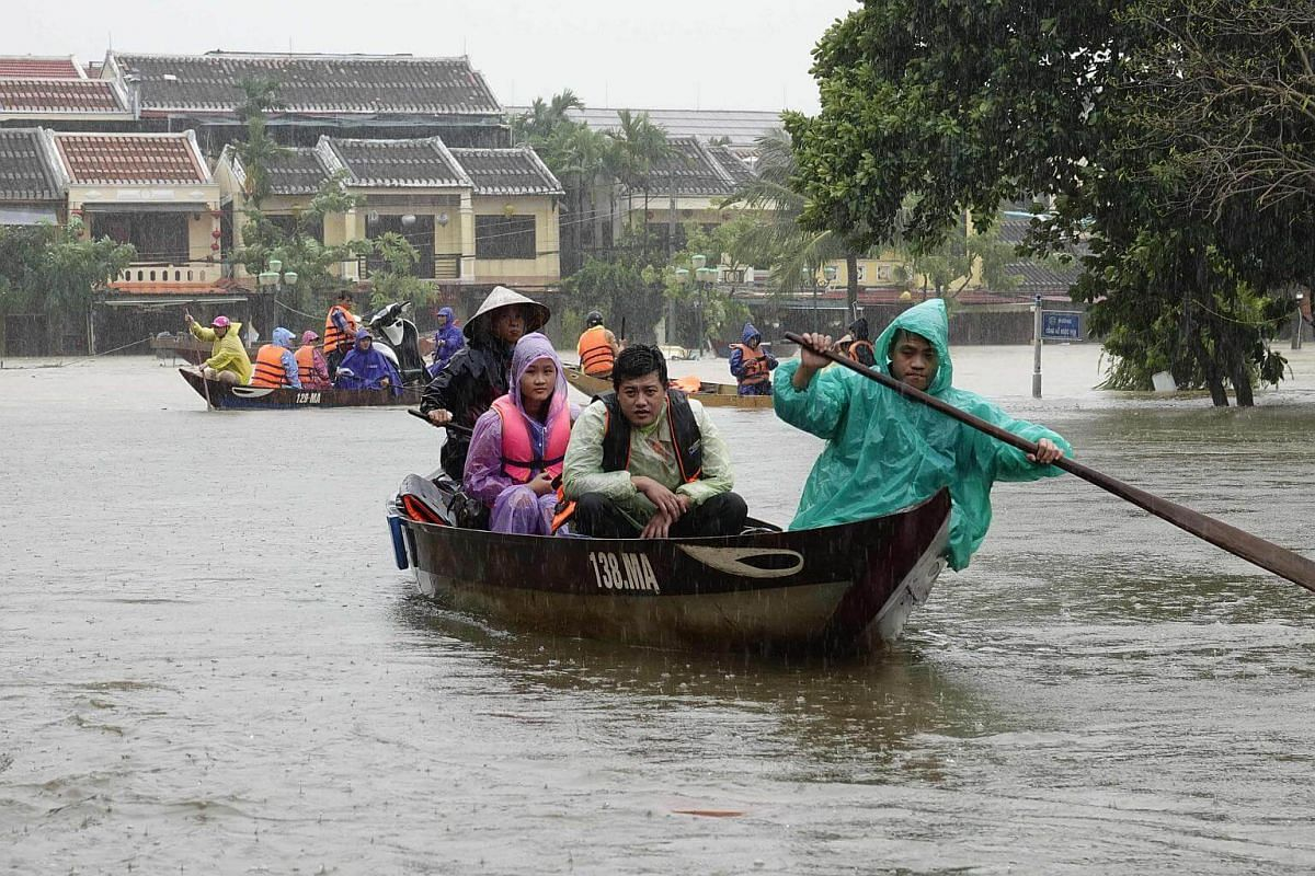 Residents and tourists are transported by boats through floodwaters in the tourist town of Hoi An, Vietnam.