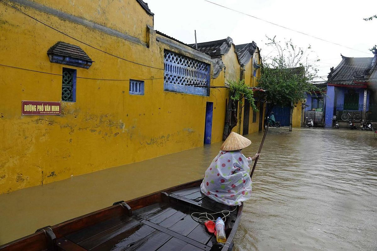 A woman rows a boat through floodwaters in the tourist town of Hoi An, Vietnam.