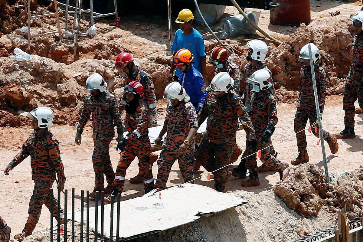 Rescue workers carry the body of a landslide victim at a construction site in Tanjung Bungah, Penang, Malaysia.