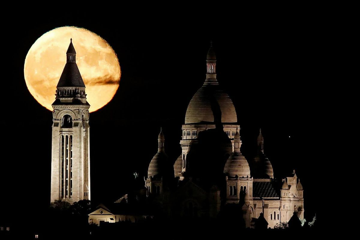 The moon rises over the Sacre Coeur Basilica in Montmartre in Paris.