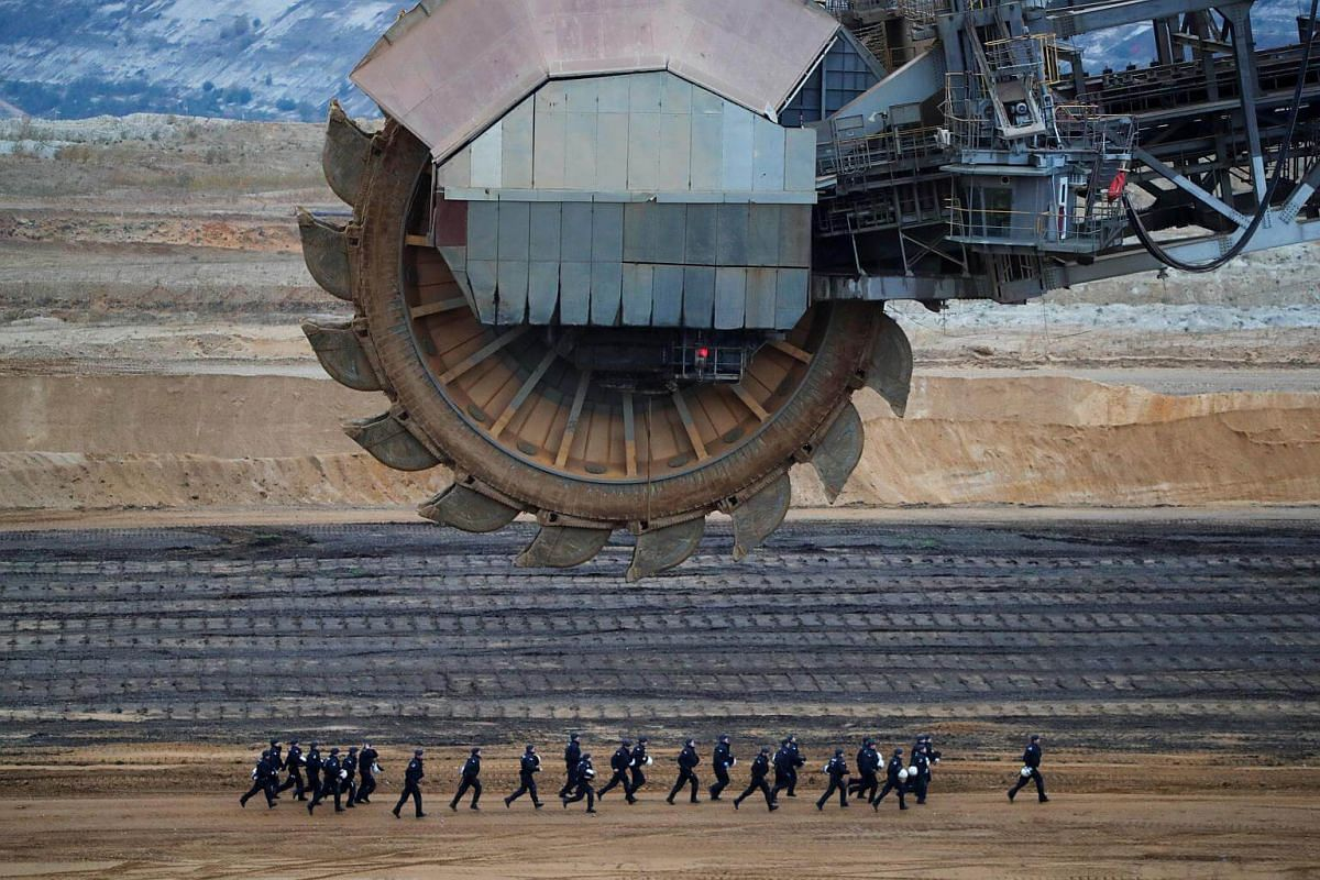 Riot police run past an excavator, during a demonstration against open-cast brown coal mining of Garzweiler, Germany.