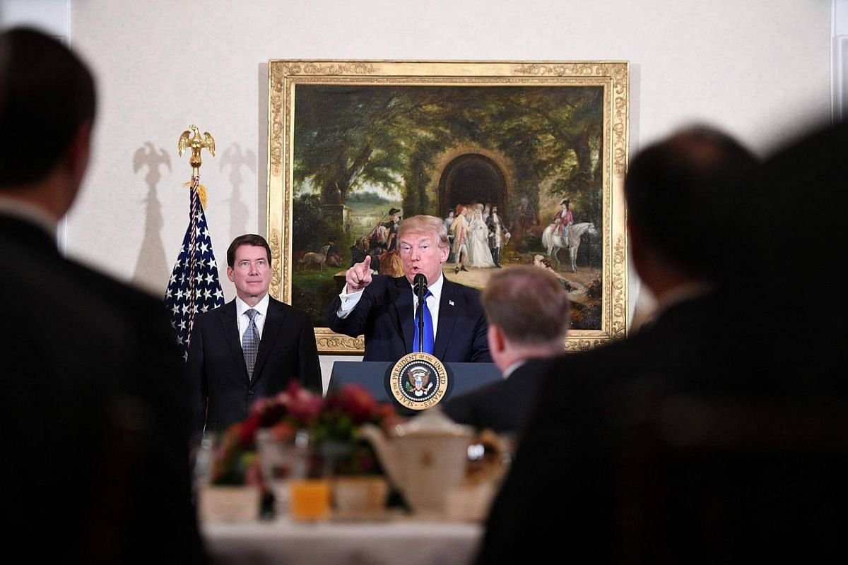 US President Donald Trump addresses US and Japanese business leaders as US Ambassador Bill Hagerty (left) watches on, in Tokyo, on Nov 6.