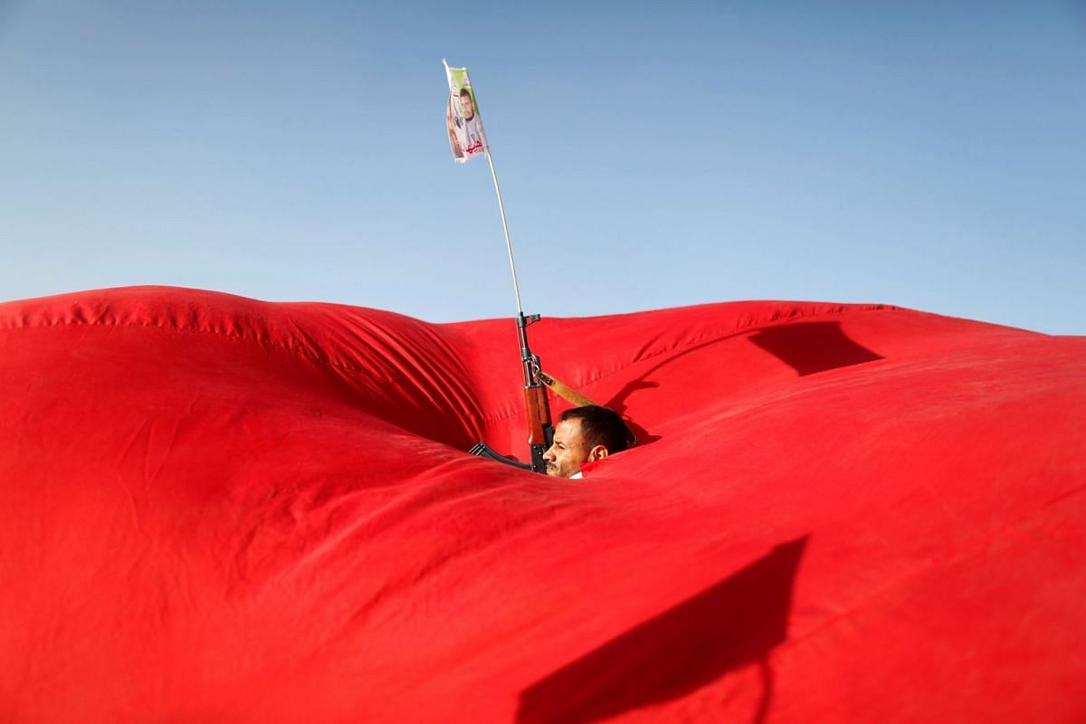 A Houthi follower emerges from a gap in a flag as he attends a rally to show support to the Palestinians in Sanaa, Yemen November 6, 2017.